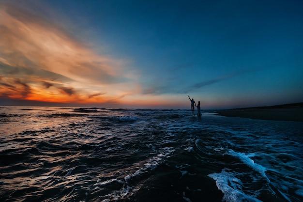 Ein verliebtes paar bei sonnenuntergang auf dem hintergrund des meeres, ein nicht wiedererkennbares paar