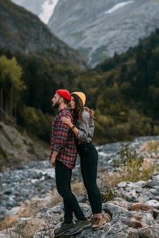 Ein verliebtes paar, das in die berge reist. paare, die in den bergen stillstehen. ein spaziergang in den bergen. ein mann und eine frau umarmen sich vor dem hintergrund der natur. platz kopieren.