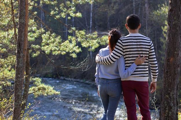 Ein verliebtes paar, ein mann und ein mädchen stehen in der natur in der nähe des flusses und freuen sich.
