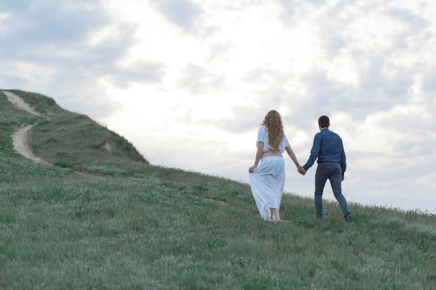 Ein verliebtes paar, eine schwangere frau in einem weißen outfit gehen auf einem hügeligen feld spazieren. bedecktes wetter,