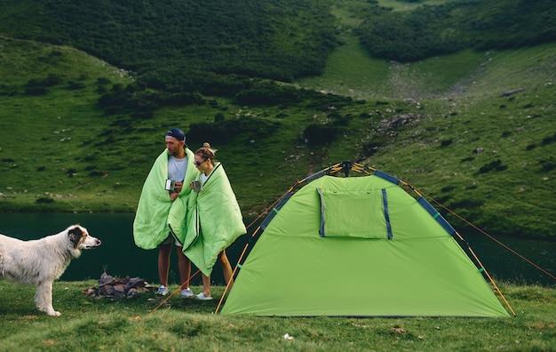 Ein verliebtes paar, eingehüllt in warme decken mit tassen kaffee oder tee, steht in der nähe eines zeltes am see. ein paar touristen mit hund in den bergen. reisen, urlaub, tourismus.