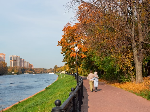 Ein verliebtes paar mittleren alters geht in einer umarmung den herbstdamm entlang.