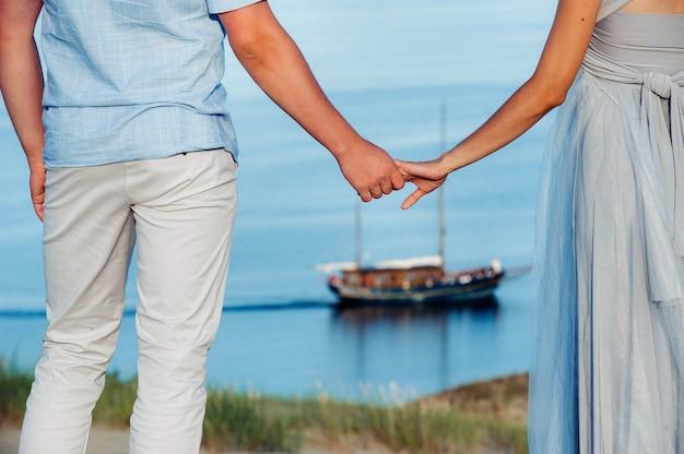 Ein verliebtes paar steht am strand in den dünen vor dem hintergrund der ostsee und einem schiff