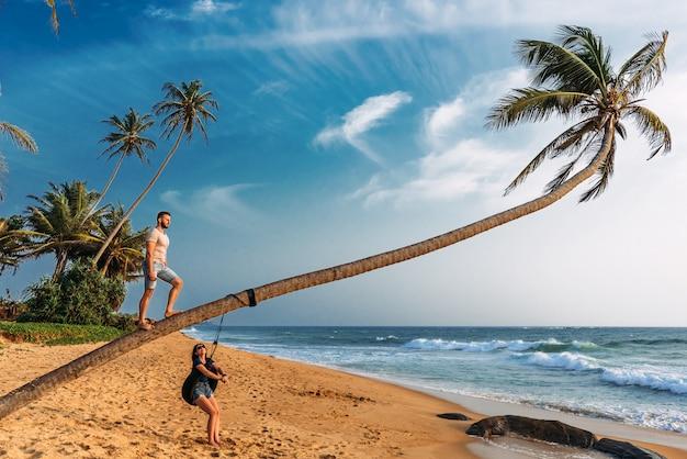 Ein verliebtes paar trifft den sonnenuntergang am strand mit palmen. hochzeitsreise. mann und frau in asien unterwegs. mann und frau, die in sri lanka stillstehen. paar verliebt bei sonnenuntergang. paar auf der insel