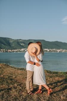 Ein verliebtes paar umarmt sich nach ihrer verlobung am strand im sonnenuntergang. küsse das brautpaar, bedeckt mit einem hut. ein mädchen in einem weißen kleid mit einem mann an einem romantischen ort