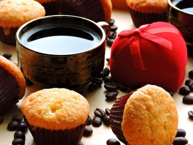 Ein verlobungsring in einem roten etui, zwei tassen kaffee und ein cupcake. konzept heiratsantrag. frühstück zum valentinstag.