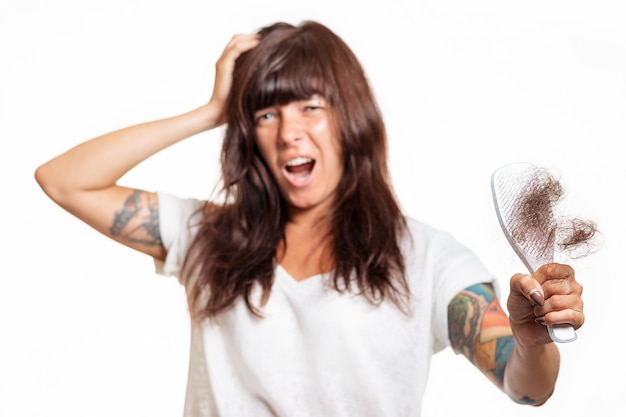 Ein verschwommenes porträt einer tätowierten frau hält einen kamm mit herausgezogenem haar und hält ihren kopf und schreit vor schmerzen. weißer hintergrund. konzept zur haarpflege.
