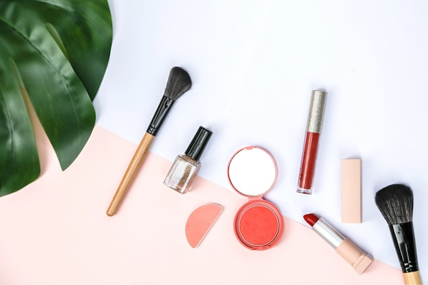 Ein verspottender satz einiger kosmetischer produkte mit süßem rosa und weißem papier