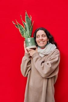 Ein vertikales foto einer schönen frau, die einen topf mit schlangenpflanzen auf roter wand hält