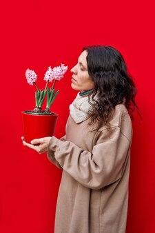 Ein vertikales foto einer schönen frau riecht einen topf mit hyazinthenpflanzen an der roten wand