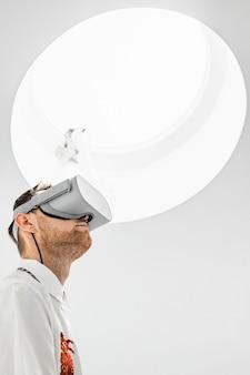 Ein vertikales foto mit niedrigem winkel eines futuristischen kühlen männlichen arztes, der vr-brille in einem krankenhaus trägt
