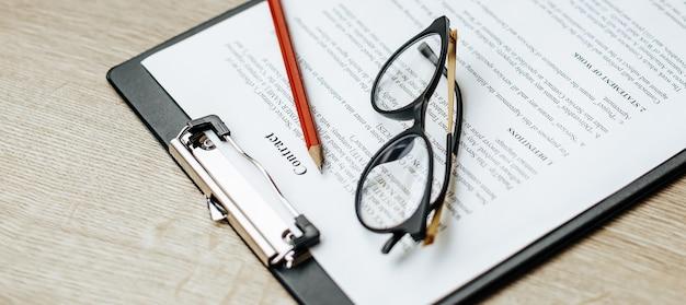 Ein vertrag auf einem hölzernen arbeitstisch mit brille und rotstift. die dokumente sind zur unterzeichnung bereit. geschäftskonzept. kooperationsvereinbarung.