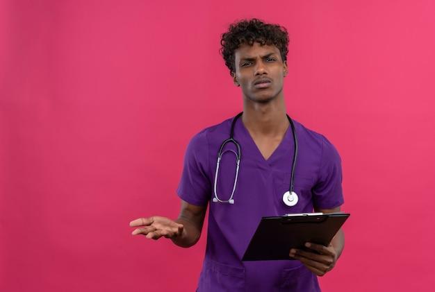 Ein verwirrter junger gutaussehender dunkelhäutiger arzt mit lockigem haar in violetter uniform mit stethoskop, das wütend auf die kamera schaut, während er die zwischenablage hält