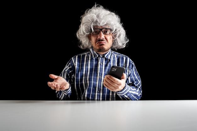 Ein verwirrter senior, typischer boomer, versteht nicht, wie man das smartphone auf schwarzem hintergrund bedient