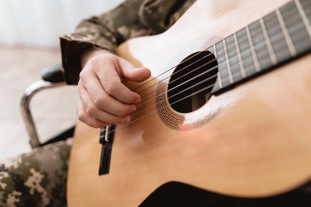 Ein veteran im rollstuhl spielt gitarre.
