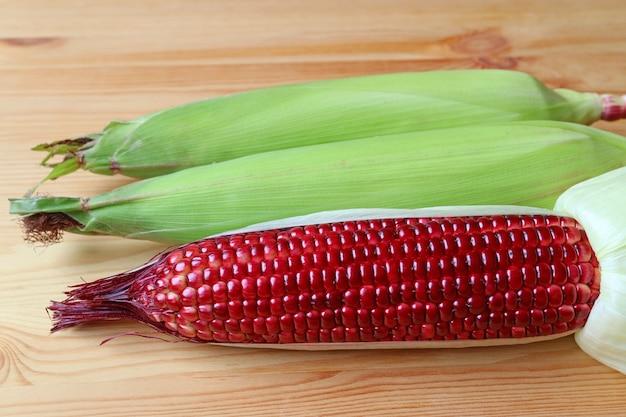 Ein vibrierender farbfrischer purpurroter mais mit zwei purpurroten körnern in den grünen hülsen auf dem holztisch