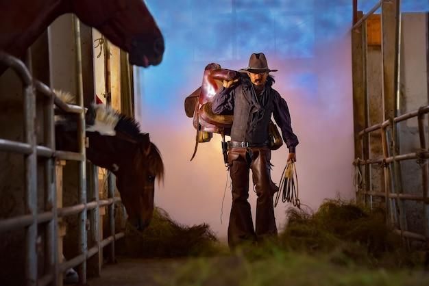 Ein vintages bild eines cowboymannes, der einen sattel in seinem stall trägt.