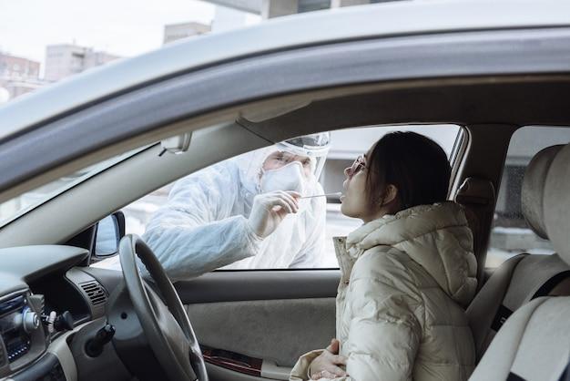 Ein virologe oder arzt, der schutzkleidung für psa-gefahrstoffe trägt, entnimmt eine probe eines pcr-tests