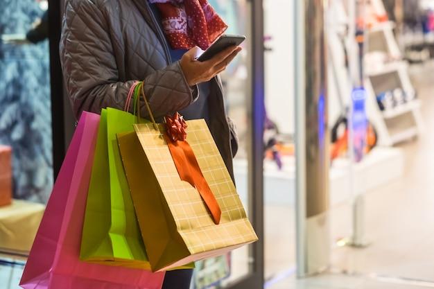 Ein volk allein. eine ältere frau genießt das abendliche einkaufen und nutzt dabei angebote und rabatte. auf seinem arm viele einkaufstüten während sie auf ihr handy schaut
