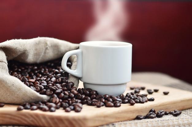 Ein voller beutel braune kaffeebohnen und eine weiße schale heißer kaffee liegt auf einer holzoberfläche