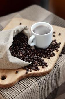 Ein voller sack braune kaffeebohnen und eine weiße tasse heißen kaffee l