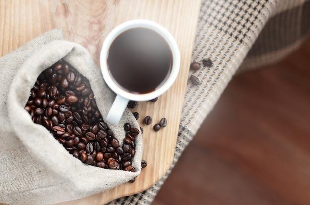 Ein voller sack braune kaffeebohnen und eine weiße tasse heißen kaffee
