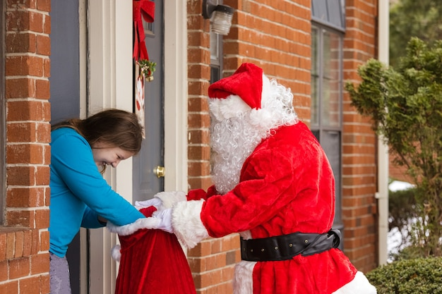 Ein von kindern, die geschenkbox einen weihnachtsmann geben, feiern weihnachten weihnachten