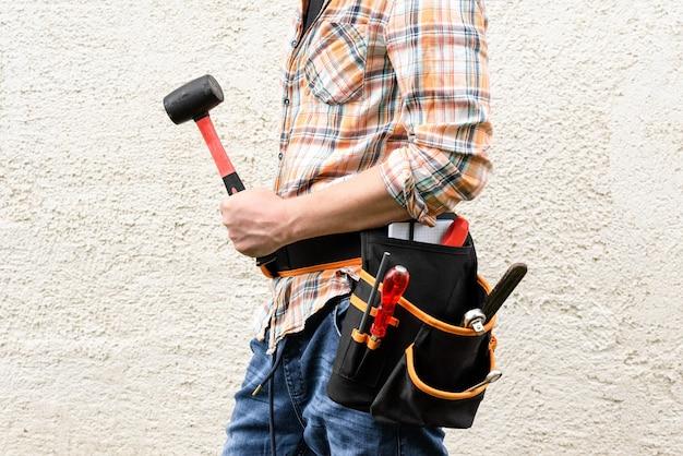 Ein vorarbeiter mit einem werkzeuggürtel hält einen gummihammer.