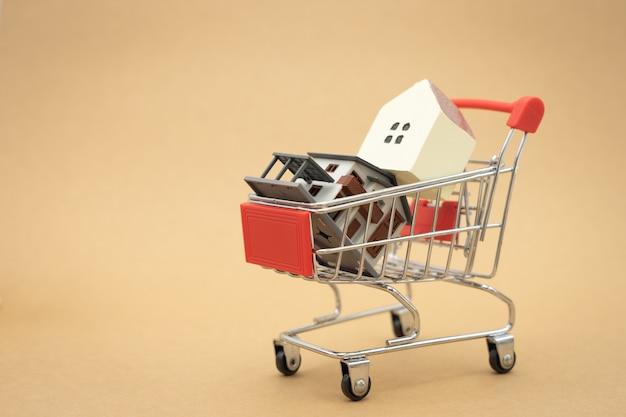 Ein vorbildliches hausmodell wird auf einen warenkorb im einkaufszentrum gesetzt, das als hintergrundgeschäftskonzept verwendet