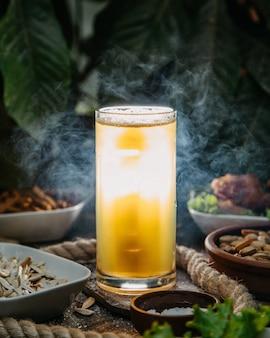 Ein vorderansicht-eiscocktail in langem glas mit geschirr und nüssen auf dem tisch trinken saftcocktail-eisfleisch