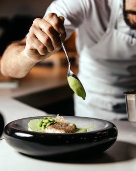 Ein vorderansicht-koch, der essen innerhalb des küchenlebensmittel-mahlzeit-frittierkochs zubereitet