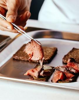 Ein vorderansicht-koch, der fleischabdeckungsmahlzeit innerhalb der platte vorbereitet, brät fleischnahrungsmittelmahlzeit