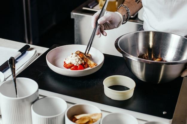 Ein vorderansicht-koch, der mahlzeit im weißen anzug und in den handschuhen vorbereitet, die fleischmehl innerhalb des küchenlebensmittelmahlzeitfleischs entwerfen