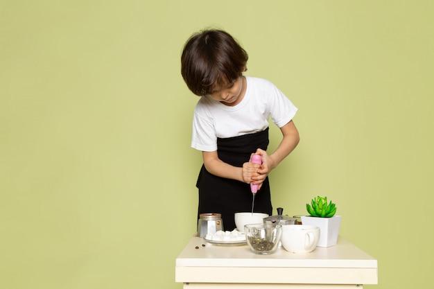 Ein vorderansicht-kochjunge im weißen t-shirt bereitet kaffee und getränk auf dem steinfarbenen raum vor