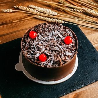 Ein vorderansicht-schokokuchen verziert mit schokoladencreme-roten kirschen innerhalb des braunen kuchenpfannenfeiertags köstlichen geburtstages auf dem braunen hintergrund