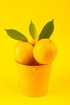 Ein vorderansichtkorb mit zitronen frisch reif mit grünen blättern isoliert auf der gelben hintergrund zitrusfruchtfarbe