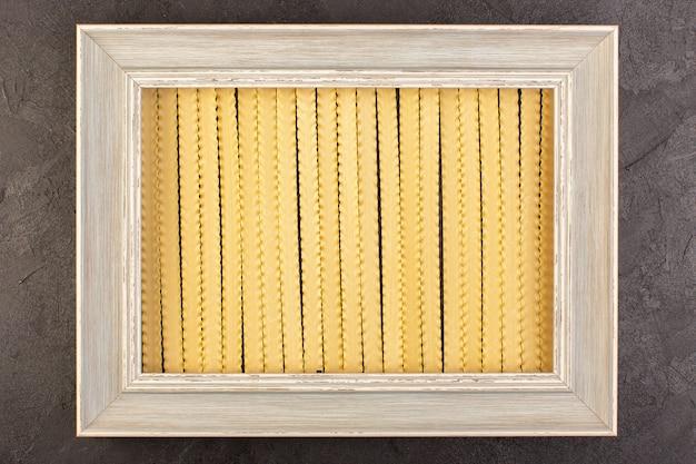 Ein vorderansichtrahmen mit pasta grauem fotorahmenquadrat gebildet lokalisiert auf den dunklen hintergrundfoto-nahrungsmittelnudeln