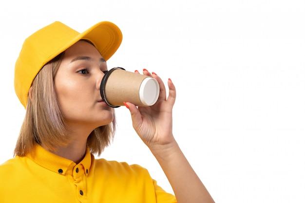 Ein vorderer blick weiblicher kurier, der kaffee auf weißem hintergrunddienst trinkt, liefert