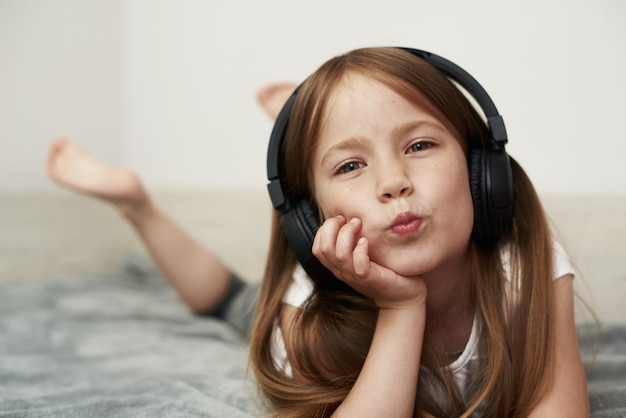 Ein vorschulkind hört musik auf ihrem bett