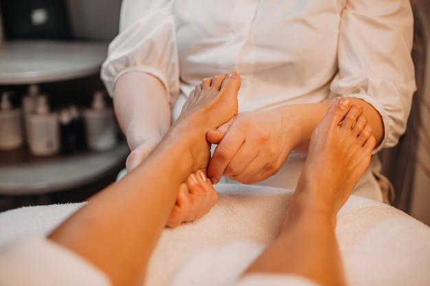 Ein vorsichtiger masseur massiert die füße des kunden während eines anti-aging-spa-verfahrens
