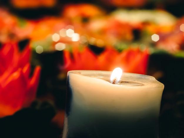 Ein wachs oder talg mit einem zentralen docht, der beleuchtet wird, um beim brennen licht zu erzeugen. viele brennende kerzen mit geringer schärfentiefe