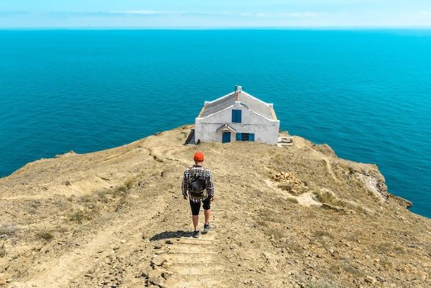 Ein wanderer mit rucksack steigt vom berg zum haus am meer hinab