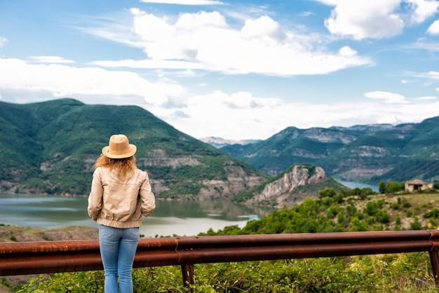 Ein wandermädchen steht am straßenrand und schaut auf den fluss und die berge. lage: die mäander des flusses arda, bulgarien