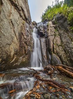 Ein wasserfall in einer wilden bergschlucht