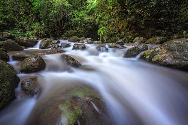 Ein wasserfall ist ein ort, an dem wasser über einen senkrechten tropfen im verlauf eines baches fließt.