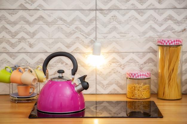 Ein wasserkocher auf einem zwei-flammen-herd in einer hellrosa küche im skandinavischen stil.
