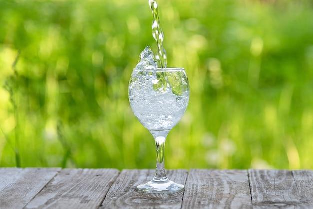 Ein wasserstrahl fließt in das glas.