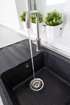 Ein wasserstrahl fließt vom wasserhahn zum spülbecken in der küche.