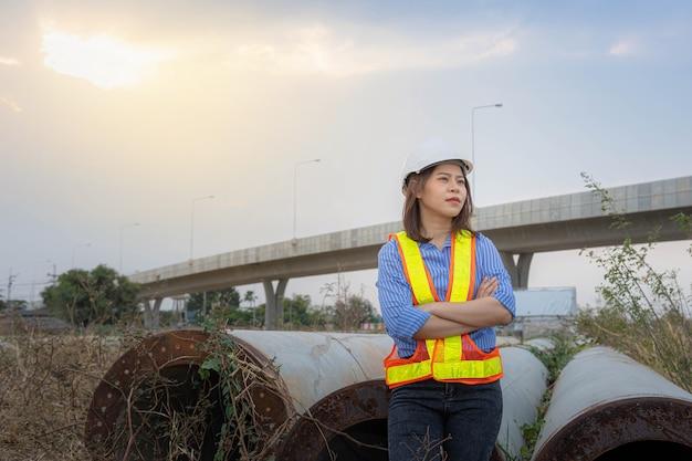 Ein weiblicher architektenführer, der einen schutzhelm trägt, der auf der brückenbaustelle steht.