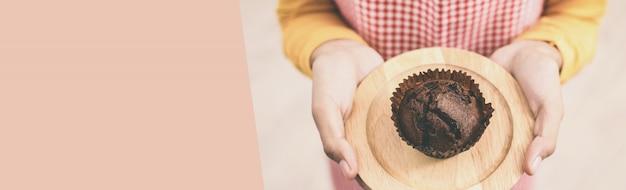 Ein weiblicher bäcker, der ein selbst gemachtes schokoladenkuchenmuffin darstellt. panorama banner mit textfreiraum